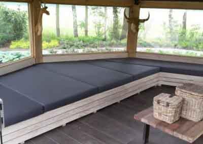 Op maat gemaakte bank met bijpassende kussens in prieel